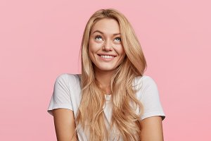 Cheerful blonde female looks upwards, has shining smile, thoughtful expression, dressed in casual white t shirt, isolated over pink studio background. Beautiful young woman dreams about something