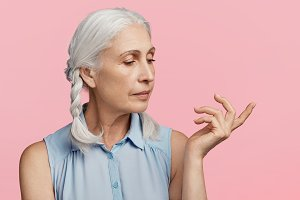 Isolated shot of serious mature woman has confident expression, looks aside and indicates at something, isolated over pink background. Elderly female deep in thoughts, thinks about hard life
