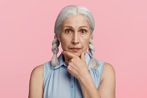 Mature confident serious woman with grey pigtails, wears fashionable blouse, watches news attentively, keeps hand on chin, isolated over pink background. Advanced age. Wrinkled female pensioner