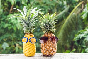 Couple of funny attractive pineapples in glasses and glasses for swimming on a tropical terrace. tropical island