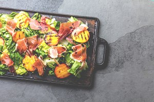 Lettuce, ham serrano and grilled peaches salad served on black board. Top view