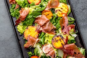 Lettuce, ham serrano and grilled peaches salad served on black board with red wine. Top view