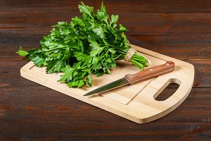 A bunch of green parsley on a wooden table with a knife.