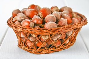 Walnut hazelnuts in a wicker basket on a white wooden table.