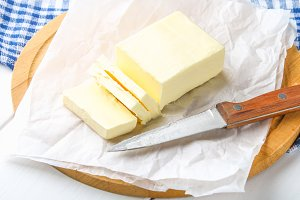 A bar of butter on a wooden board with a knife, on a white table. Ingredients for cooking.
