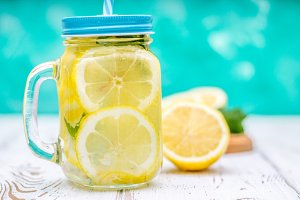 Banks with handles with cold lemonade on a white wooden background. Lemons.