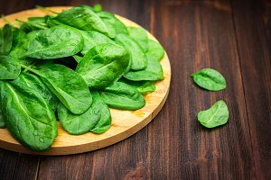Fresh juicy spinach leaves on a wooden brown table. Natural products, greens, healthy food, vitamins.
