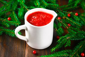 Cowberry cranberry sauce in a glass white sauceboat on a wooden table with spruce branches.