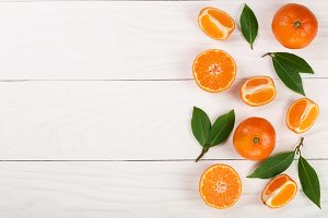tangerine with leaves on white wooden background with copy space for your text. Flat lay, top view. Fruit composition