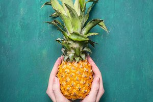 fresh pineapple in hands of a girl