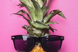 small ripe pineapple with sunglasses