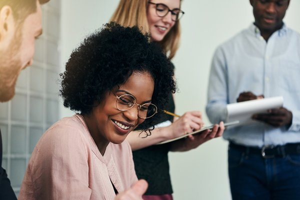 Business Stock Photos: Stefan & Janni - Smiling African businesswoman working with colleagues in an office