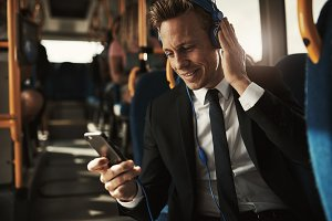 Smiling businessman listening to music during his morning commute