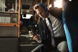 Young businessman wearing headphones and reading messages on the bus