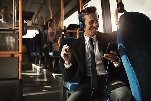 Young businessman sitting on a bus listening to music