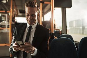 Smiling young businessman standing on a bus sending text messsages
