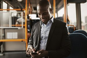 Young African businessman listening to music during his morning commute