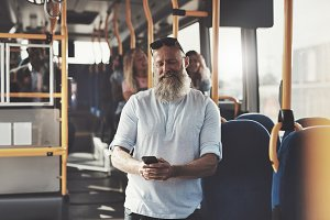 Mature man laughing at a text message on the bus