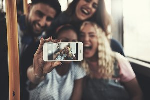 Smiling friends taking selfies with a smartphone on the bus