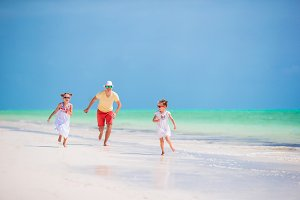Family walking on white beach on caribbean island. Father have fun with daughters on the beach