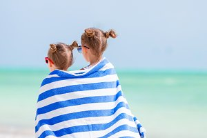 Adorable little girls wrapped in towel at tropical beach after swimming in the sea