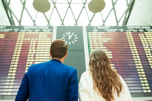 Young man and woman in international airport looking at the flight information board