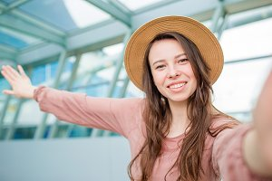 Young woman taking selfie an airport lounge waiting for boarding in international airport