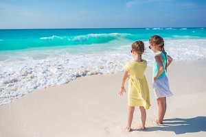 Little girls at tropical beach playing together on the seashore