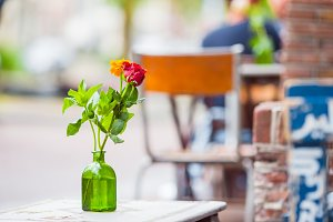Glass vase with a flower on the table at outdoor restaurant