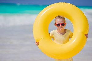 Portrait of little girl with inflatable rubber circle on beach vacation