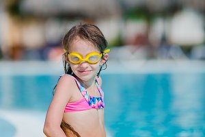 Little girl with inflatable rubber circle in outdoor swimming pool