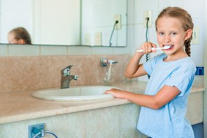Little smile girl brushes teeth in the bathroom