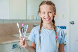 Little beautiful girl with white teeth brushes teeth in the bathroom