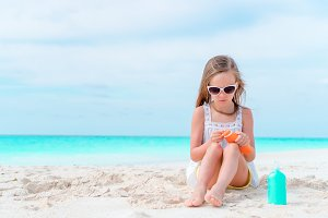 Little adorable girl with suncream bottle on the beach
