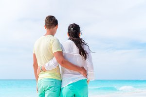 Young couple on white beach during summer vacation. Happy family enjoy their vacation