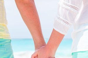 Young couple holding hands at tropical beach. Closeup male and female hands