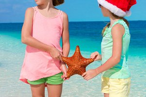 Adorable little girls on Christmas beach vacation. Kids with starfish background the blue sky and turquiose sea
