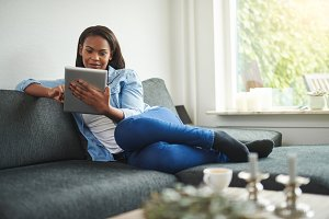 Young African woman relaxing at home with a digital tablet
