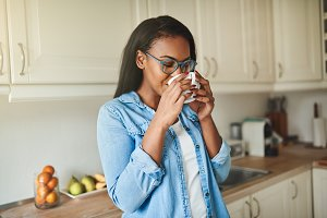 Young African woman enjoying a coffee in her kitchen