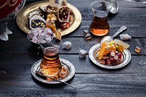 Cups of Turkish tea with oriental sweets on rustic wood