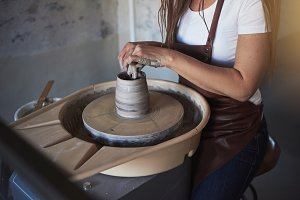 Creative artisan shaping wet clay on a pottery wheel