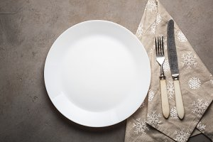Empty plate with cutlery and beige towel with snowflakes on the stone table. Overhead view