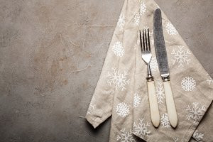 Vintage Cutlery and beige towel with snowflakes on the stone table. Top view with copy space