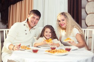 Family eating dinner at a dining table, Round table, pizza, orange, house made of wood