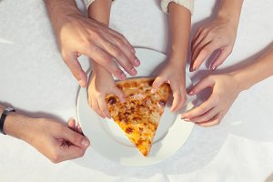 People Hands Grabbing Pizza from white plate