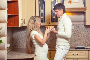 Caring couple eating pizza together, pregnancy, in white clothes.