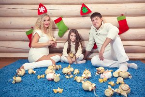 Beautiful family in Christmas interior, pregnancy, in a wooden house