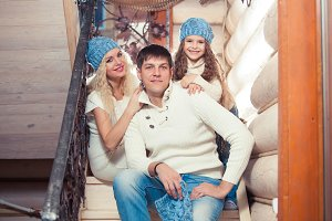 happy family mother, father, child daughter at home, in a winter sweater and hat, the concept of Christmas. on the stairs