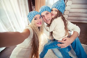 holidays, technology and people concept - happy family sitting on floor and taking selfie picture with smartphone at home, in a winter sweater and hat, the concept of Christmas