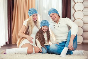 Young family sitting on floor. in a winter sweater and hat, the concept of Christmas. pregnancy in a wooden house